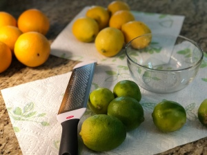 A kitchen counter with oranges, lemons and limes, washed and on paper towels. A bowl and a zester are laying there, ready for zesting to begin.