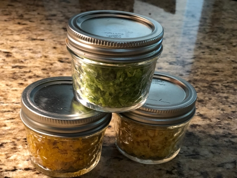 Three closed 4 oz jars of zest. One lemon and one orange zest filled jar is at the bottom and a lime filled jar sits on the top between the two others.