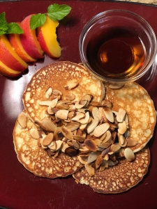 Almond pancakes, covered with toasted almonds on a dark red plate. On the side is a small bowl of warmed syrup and a sliced peach, decorated with small mint leaves.