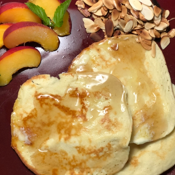Light almond pancakes with syrup on a dark red plate. On the side is a sliced peach, decorated with small mint leaves.