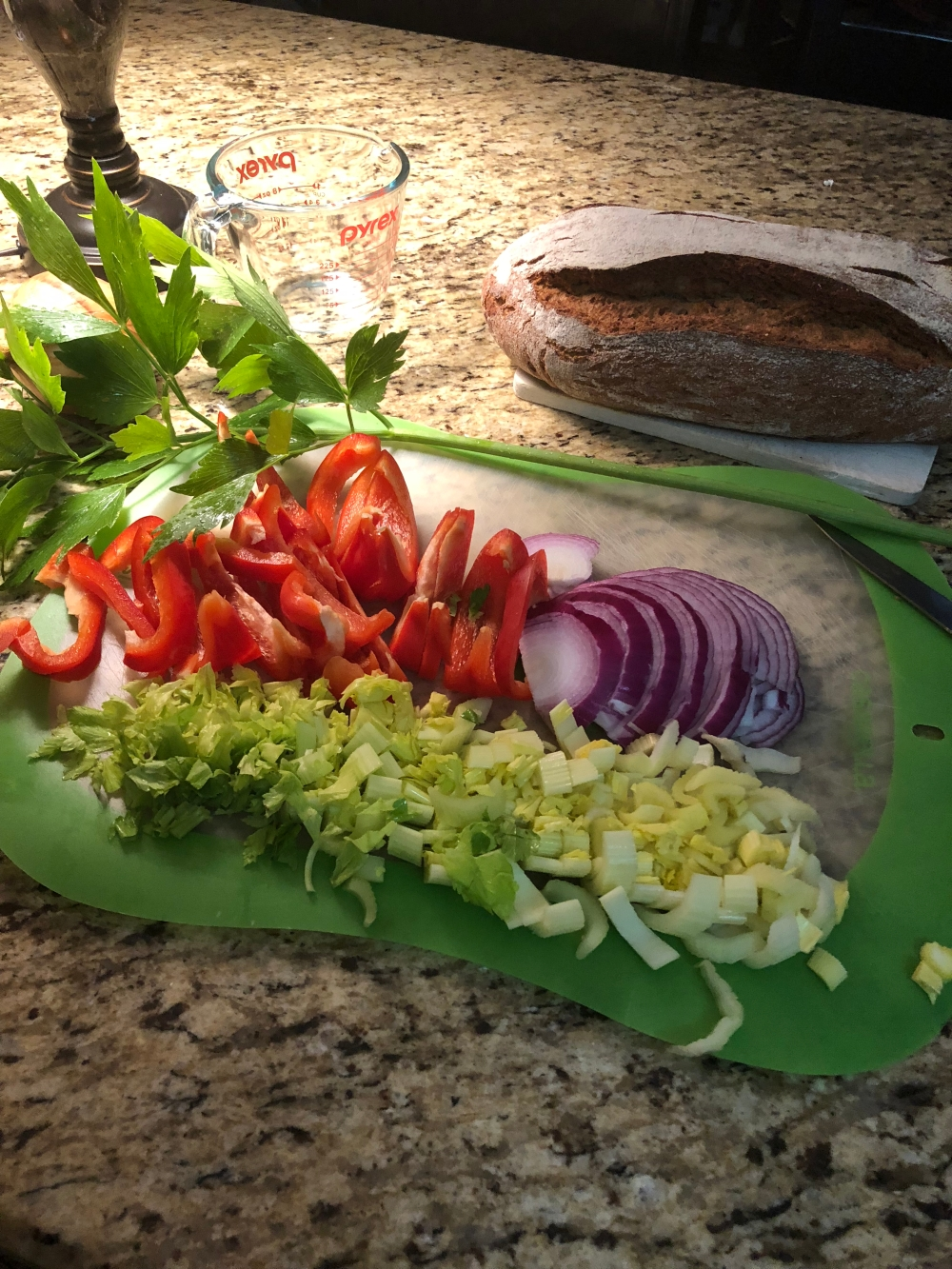 Diced celery, sliced onions, bell peppers, and a sprig of lovage, on a cutting mat. Measuring cup and freshly baked artisan bread in the background.