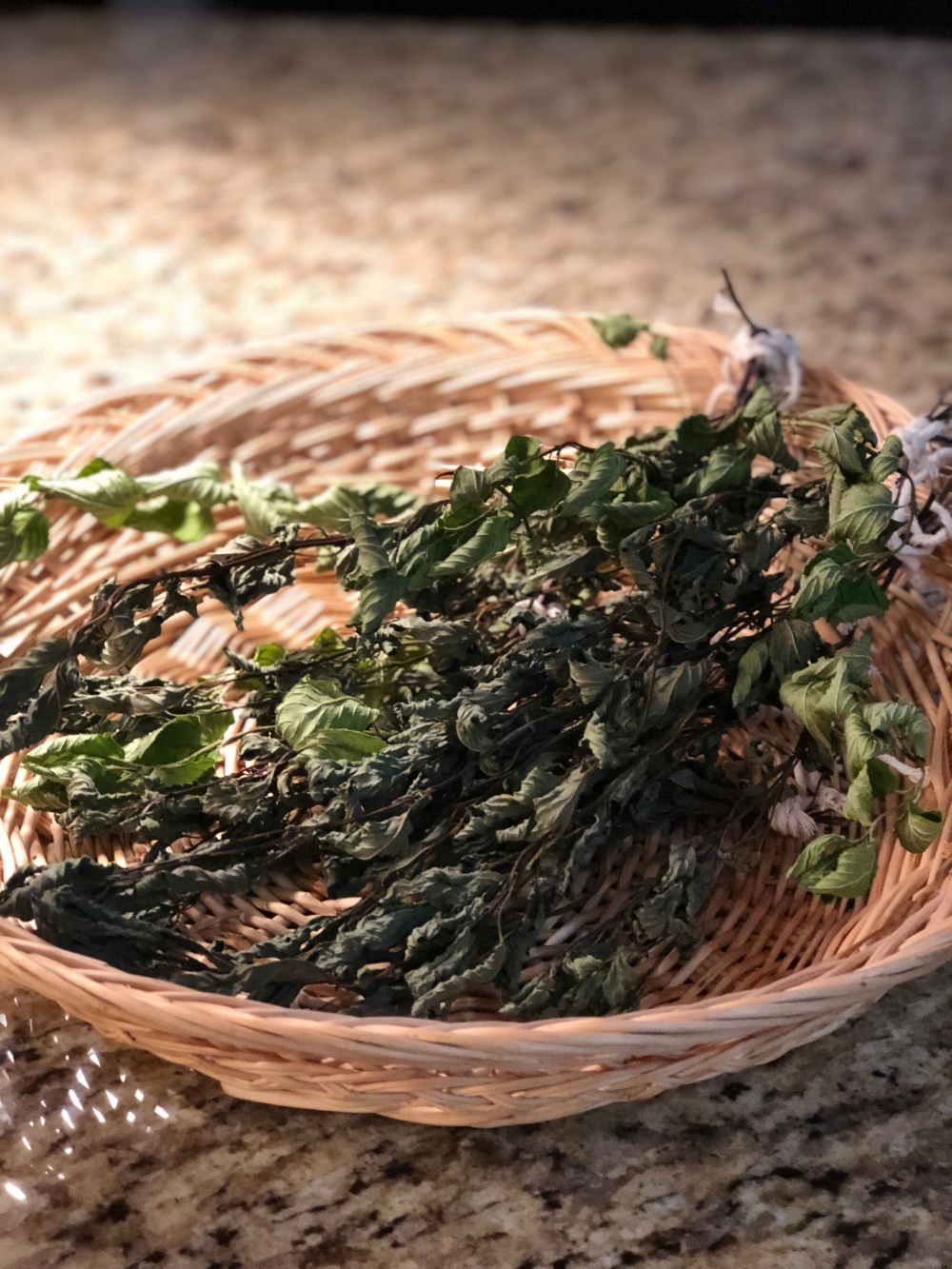 The image shows a basket filled with dried mint sprigs on a granite counter top.