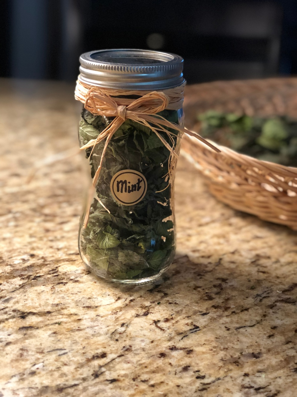 Dried mint in glass jar, labeled and decorated, on a granite counter with a basket of dried mint in the background.