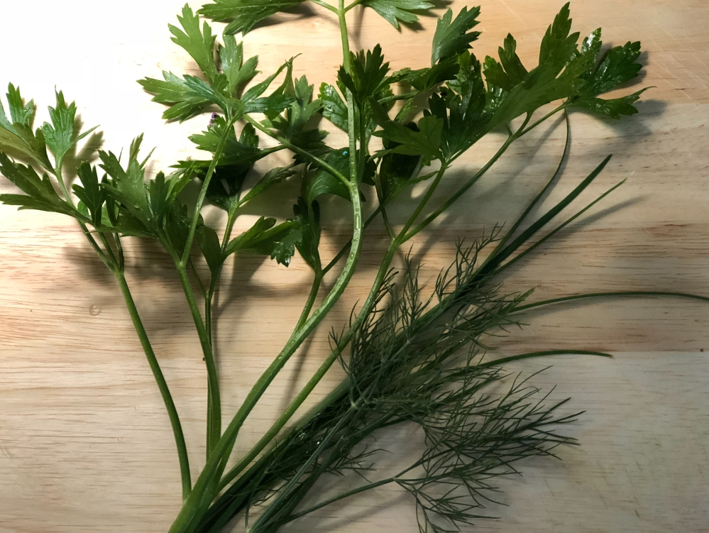Parsley, Chives, and Dill sprigs on a light wood cutting board