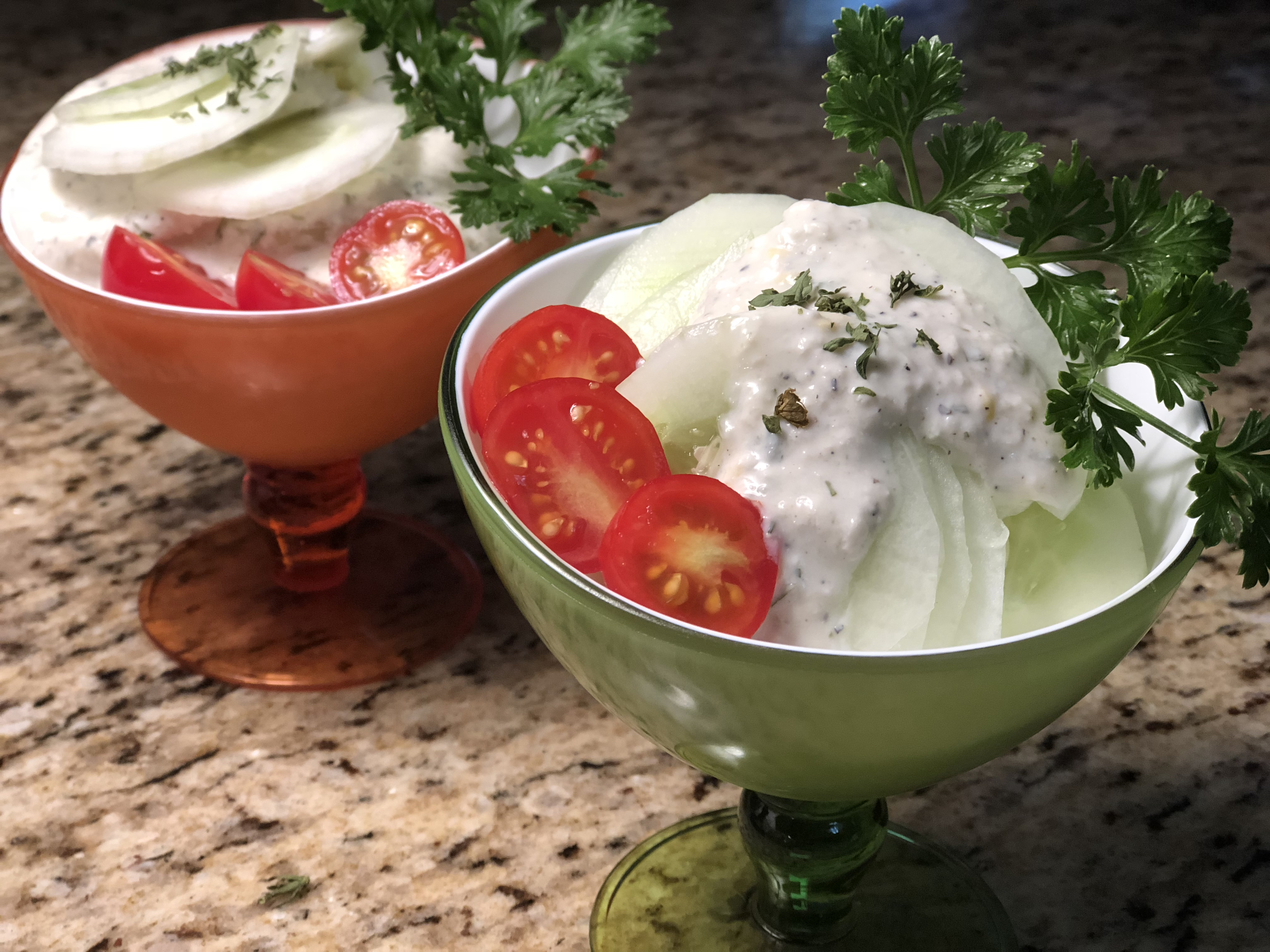 Two bowls filled with cucumber slices, topped with a white herb dressing and halved cherry tomatoes, garnished with parsley