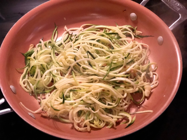 Zucchini noodles frying in a pan