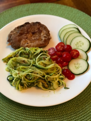 Zucchini noodles alongside pork cutlet and veggies on a white plate with green background.